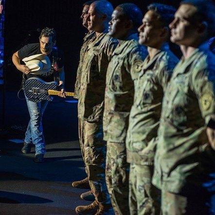Brad Paisley expressed his gratitude with a photo performing on-stage for service members.